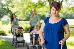 Mère avec la poussette de bébé au parc Images stock
