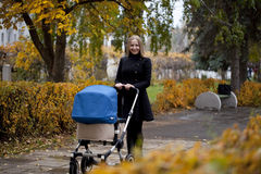 Mère avec la poussette de bébé pour un nouveau-né Photos libres de droits