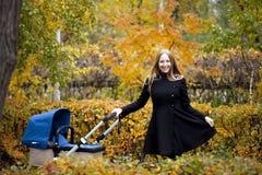 Mère avec la poussette de bébé pour un nouveau-né Photo libre de droits