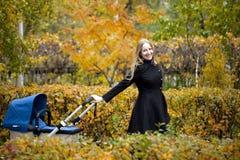 Mère avec la poussette de bébé pour un nouveau-né Photographie stock libre de droits