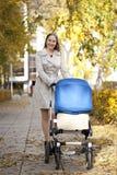 Mère avec la poussette de bébé pour un nouveau-né Images stock