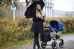 Mère avec la poussette de bébé pour un nouveau-né Photos stock