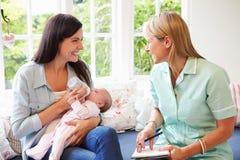 Mère avec la réunion de bébé avec le visiteur de santé à la maison photographie stock libre de droits