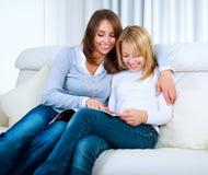 Mère avec la revue du relevé de fille adolescente Image stock