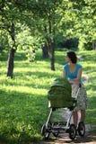 Mère avec la voiture d'enfant Photographie stock