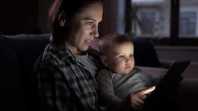 Mère avec le bébé à l'aide du comprimé numérique la nuit banque de vidéos