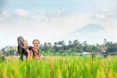 Mère avec le bébé dans le sac à dos de transport marchant sur des terrasses de riz image stock