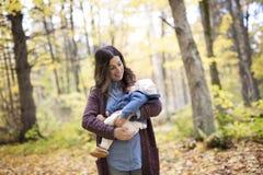 Mère avec le bébé de fille dans la forêt d'automne Photos libres de droits