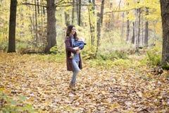 Mère avec le bébé de fille dans la forêt d'automne Image libre de droits