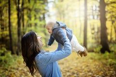 Mère avec le bébé de fille dans la forêt d'automne Photographie stock libre de droits
