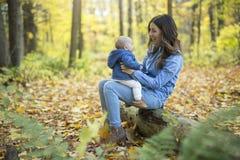 Mère avec le bébé de fille dans la forêt d'automne Image stock