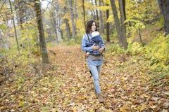 Mère avec le bébé de fille dans la forêt d'automne Images libres de droits