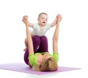 Mère avec le bébé faisant la gymnastique Image stock