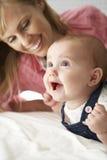 Mère avec le bébé mignon jouant sur le lit photo stock