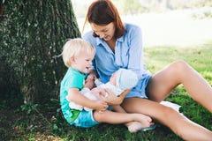 Mère avec le bébé nouveau-né et l'enfant plus âgé sur la nature Images libres de droits