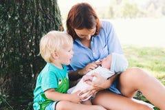 Mère avec le bébé nouveau-né et l'enfant plus âgé sur la nature Photo stock