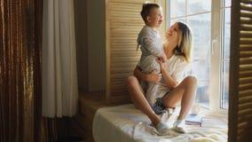 Mère avec le bébé s'asseyant à la fenêtre et au jeu Image libre de droits