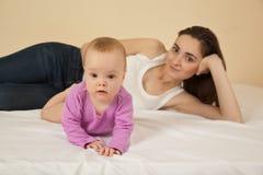 Mère avec le bébé se trouvant sur le lit Photographie stock libre de droits