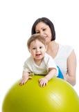 Mère avec le bébé sur la boule gymnastique Photographie stock
