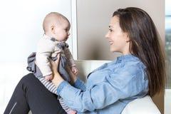 Mère avec le bébé sur le sofa prenant du bon temps Image stock