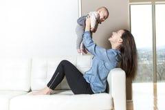 Mère avec le bébé sur le sofa prenant du bon temps Photo stock