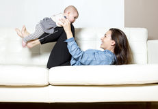 Mère avec le bébé sur le sofa prenant du bon temps Photos stock