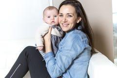 Mère avec le bébé sur le sofa prenant du bon temps Photos libres de droits