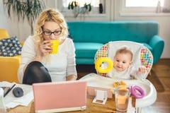 Mère avec le bébé travaillant à la maison le bureau et buvant du café Photo stock