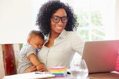 Mère avec le bébé travaillant dans le bureau à la maison Image libre de droits