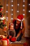 Mère avec le cadeau d'ouverture de chéri près de l'arbre de Noël Image stock