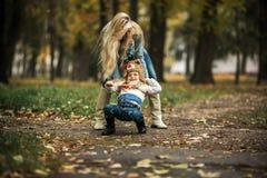 Mère avec le descendant en stationnement d'automne Photos stock