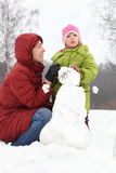 Mère avec le descendant et le bonhomme de neige Images libres de droits