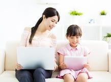 Mère avec le descendant regardant l'ordinateur portatif Image stock