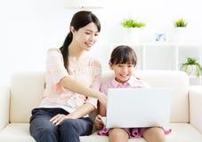 Mère avec le descendant regardant l'ordinateur portatif Photo stock