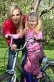 Mère avec le descendant sur la bicyclette au printemps Photos stock