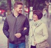 Mère avec le fils adulte marchant par la ville Images libres de droits