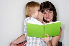 Mère avec le fils affichant le livre Photos stock