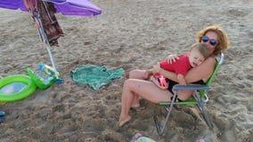 Mère avec le fils dans le coucher du soleil de plage photographie stock libre de droits