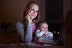 Mère avec le fils dans les bras, faisant l'appel téléphonique Image libre de droits