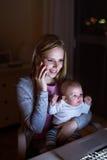 Mère avec le fils dans les bras, faisant l'appel téléphonique Images stock
