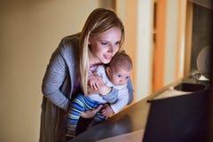 Mère avec le fils dans les bras, ordinateur portable devant elle Image libre de droits
