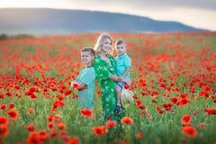 Mère avec le fils dans les pavots appréciant la vie au coucher du soleil Vacances d'été heureuses de famille Jolie brune avec la  images stock