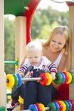 mère avec le fils de deux ans sur le terrain de jeu Photos libres de droits