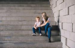 Mère avec le fils reposant sur des escaliers Photo stock