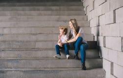 Mère avec le fils reposant sur des escaliers Photographie stock