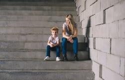 Mère avec le fils reposant sur des escaliers Photographie stock libre de droits