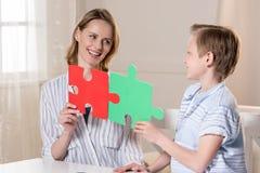 Mère avec le fils tenant des morceaux de puzzle Photographie stock libre de droits