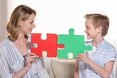 Mère avec le fils tenant des morceaux de puzzle Images stock