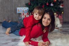 Mère avec le garçon devant un arbre de Noël Photo stock