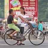 Mère avec le gros fils s'asseyant sur le porte-bagages, Pékin, Chine Photos libres de droits